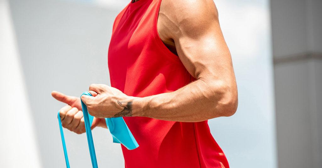 Imagen de hombre haciendo ejercicios para bíceps en casa con ligas.