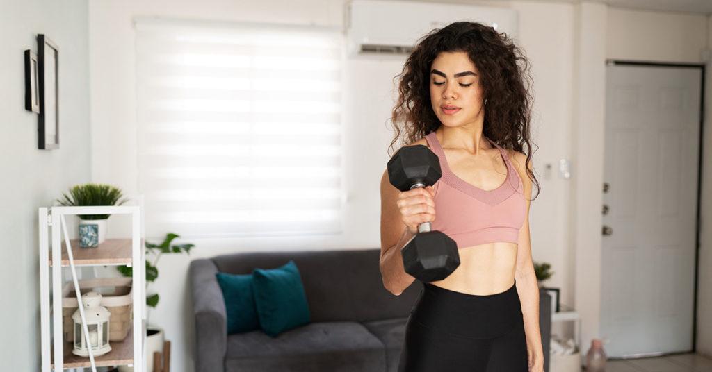 Imagen de chica haciendo ejercicios para bíceps en casa