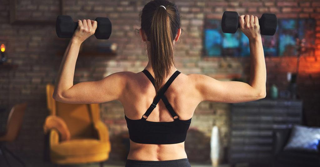Imagen de mujer ejercitando los bíceps en casa.