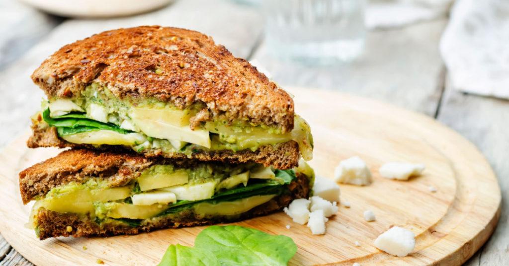 Imagen de sandwich de avena con queso de cabra y espinacas.